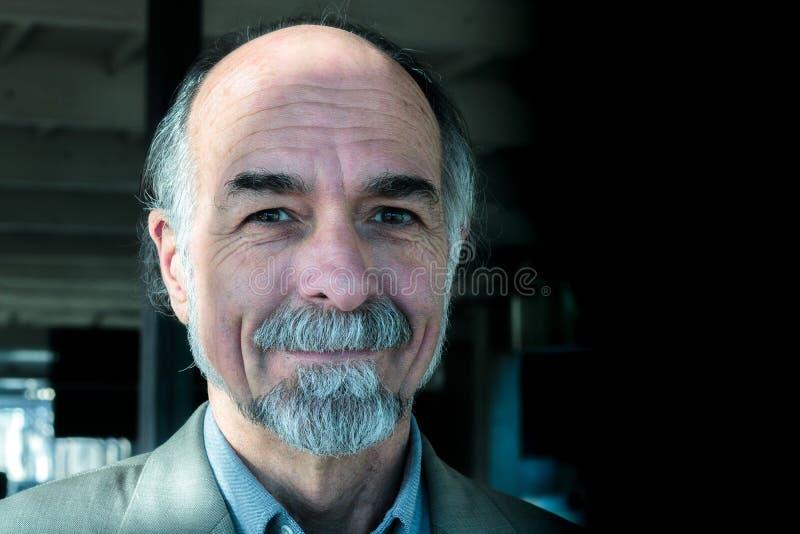 在60s的性感,迷人的可爱的资深成年男性微笑对与graying小珠,笑涡,棕色眼睛,健康资深男性p的照相机的 免版税库存图片