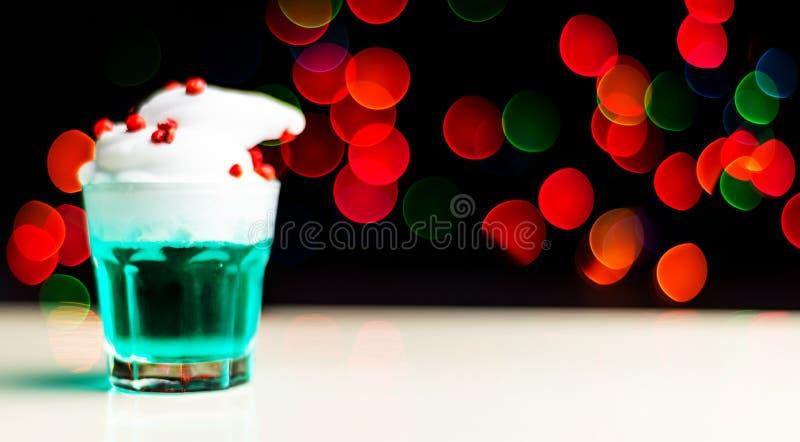 在 bokeh背景的一个小玻璃射击的圣诞节饮料,在酒吧的圣诞装饰,xmas党 免版税库存照片