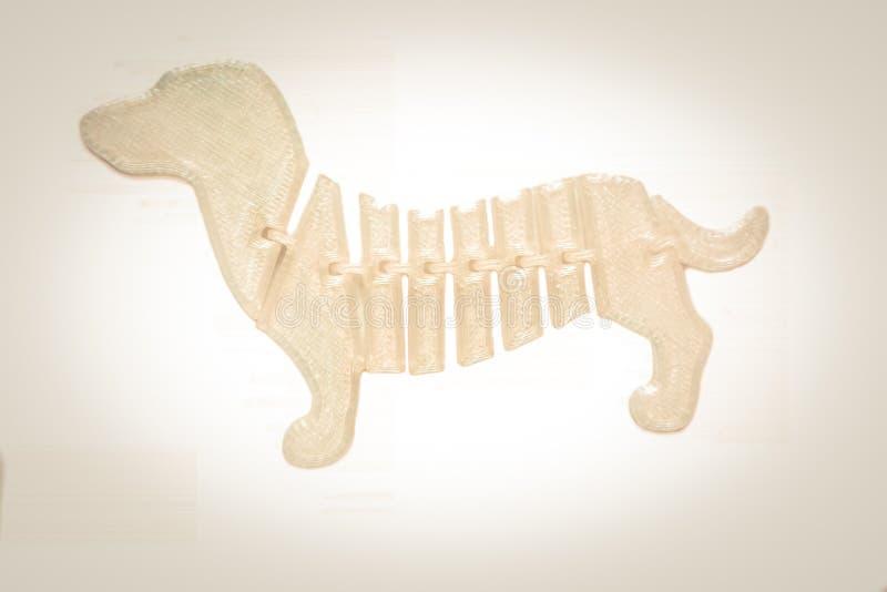 在 3d打印机打印的狗玩具形状的明亮的轻的白色对象 库存图片