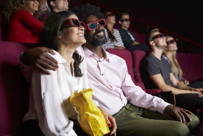 在戴3D眼镜的戏院的夫妇观看喜剧影片 免版税库存图片
