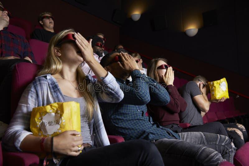 在戴3D眼镜的戏院的夫妇观看恐怖片 免版税图库摄影
