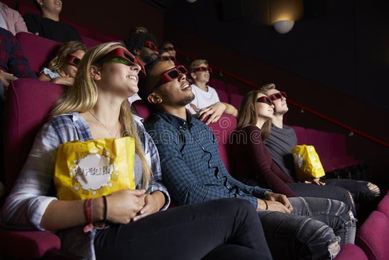 在戴3D眼镜的戏院的年轻夫妇观看影片 库存照片