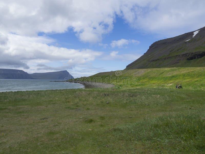 在adalvik小海湾的看法与在l的生锈的traktor和夏天村庄 库存图片