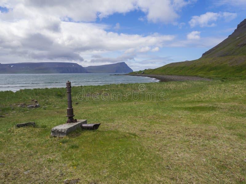 在adalvik小海湾的看法与在latrar的生锈的水泵和夏天村庄在西部海湾自然保护Hornstrandir 库存照片