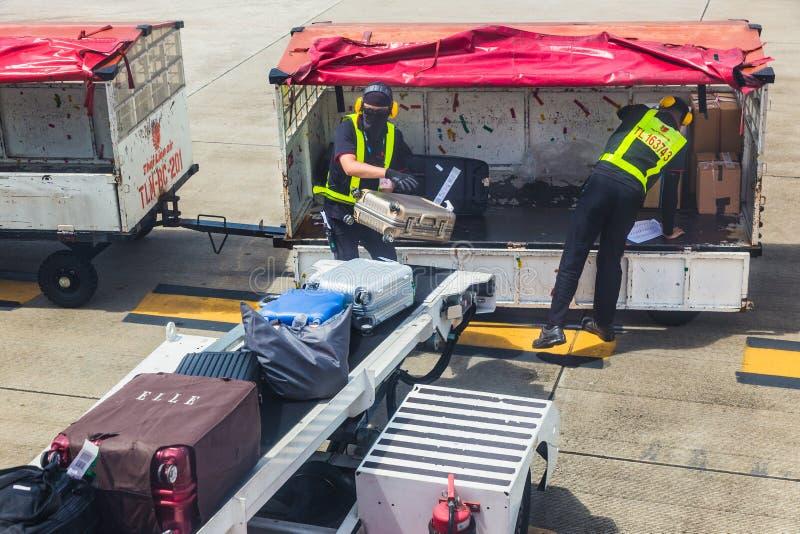 在airpla的泰国狮航地勤人员装载乘客行李 库存图片