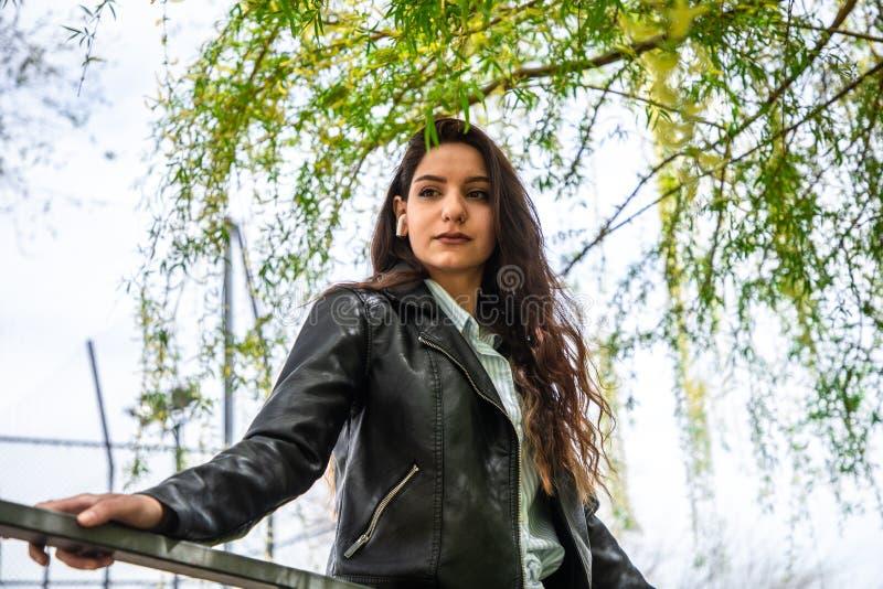 在airpods的有吸引力的女性模型在公园 免版税库存照片