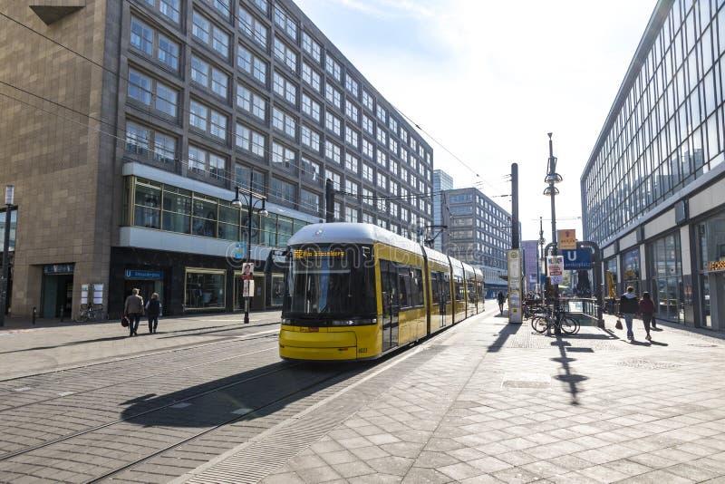 在Alexanderplatz的现代黄色电车在柏林,德国 图库摄影