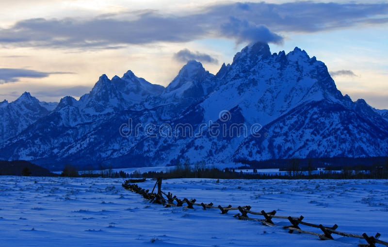 在alpenglow暮色日落的盛大Tetons分裂栅栏视图在双突透镜的云彩下在盛大Tetons国家公园在怀俄明 免版税库存图片