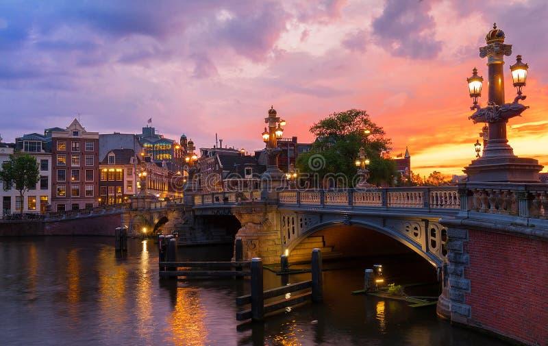 在Amstel河的Blauwbrug蓝色桥梁在阿姆斯特丹日落春天晚上,荷兰 免版税图库摄影