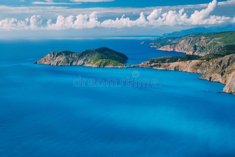 在Assos村庄前面的半岛海岸线和的Frourio 与棕色岩石石灰石costline的美丽的乳状蓝色海湾 库存照片