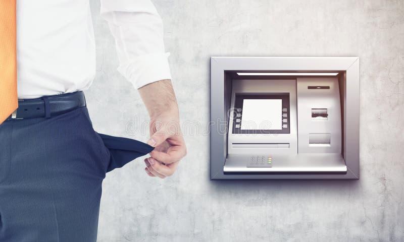 在ATM机器附近打破了商人 免版税库存图片