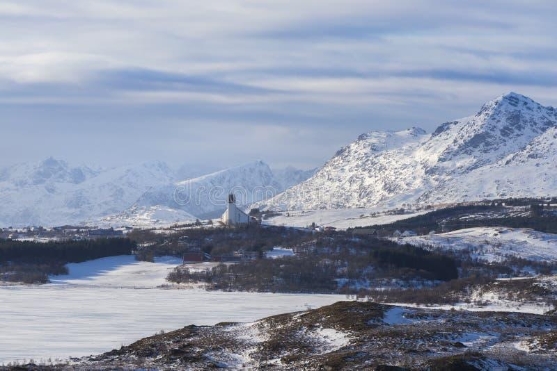 在Bøstad附近的布尔杰教会由积雪的mountai围拢了 库存照片