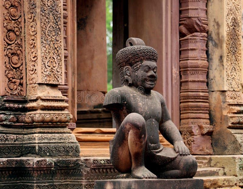在Banteay Srei红砂岩寺庙, Cambodi的监护人雕刻 库存照片