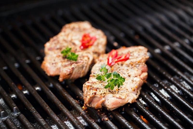 在bbq格栅的猪肉牛排与火焰 免版税图库摄影