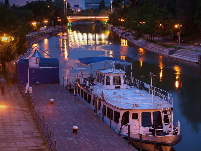 在Bega河在晚上,蒂米什瓦拉,罗马尼亚的靠码头的客船 库存照片
