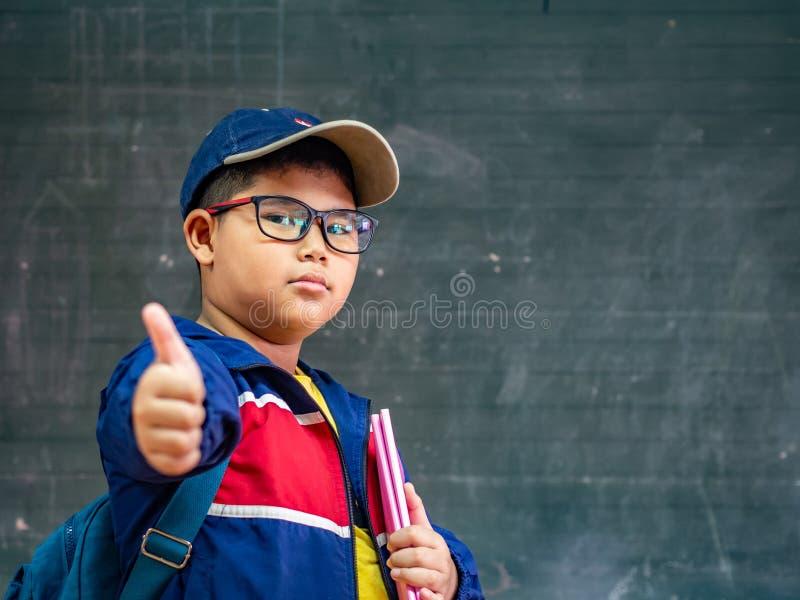 在blackbo前面的愉快的男孩穿戴玻璃微笑和立场 免版税库存照片