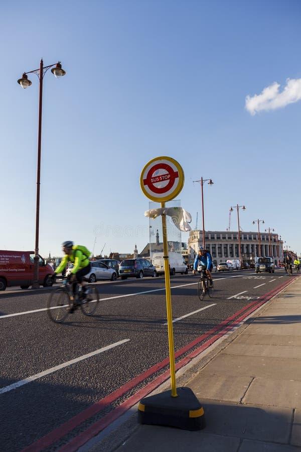 在Blackfriars桥梁的公共汽车站标志,骑自行车者在背景中 库存照片