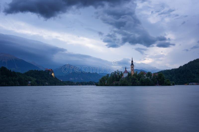 在Bled湖、海岛、教会和城堡的惊人的春天日出与山脉Stol, Vrtaca, Begunjscica 免版税库存照片
