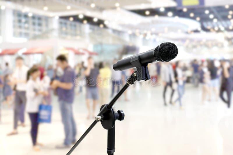 在Blurred的话筒公共关系在百货商店商城事件大厅内的许多人民在背景里面 库存照片