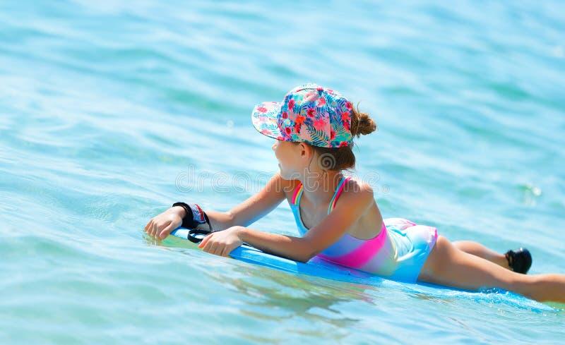 在bodyboard的愉快的小女孩游泳 库存图片