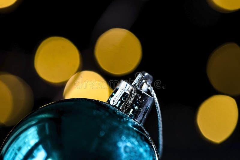 在bokeh光的蓝色圣诞节球细节,黑暗的摄影概念 免版税库存照片