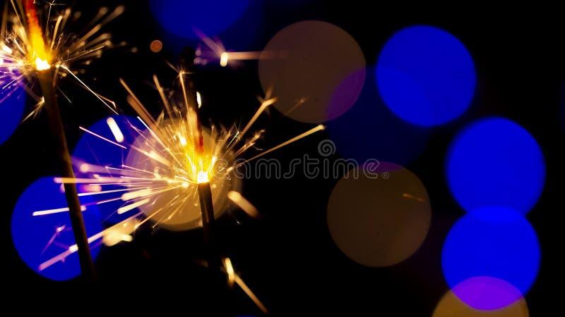 在bokeh背景的燃烧的闪烁发光物从诗歌选光  免版税库存照片