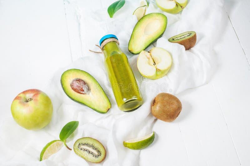 在bottl的绿色圆滑的人用鲕梨、苹果和猕猴桃在白色木背景 免版税库存图片