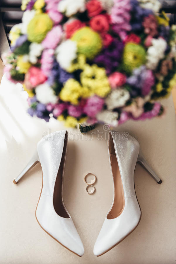 在bride& x27旁边的婚戒; s鞋子和婚礼花束 库存图片