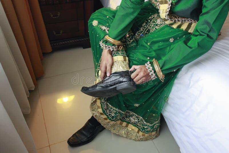 在Bugis风俗打扮的新郎人在婚姻前准备 图库摄影