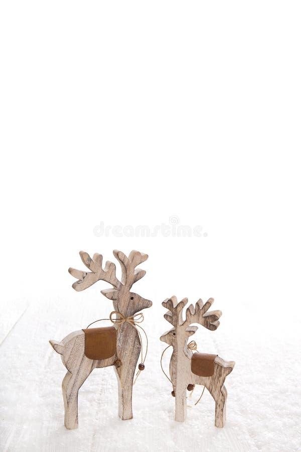 在c的白色多雪的背景隔绝的两个木被雕刻的麋 免版税库存照片