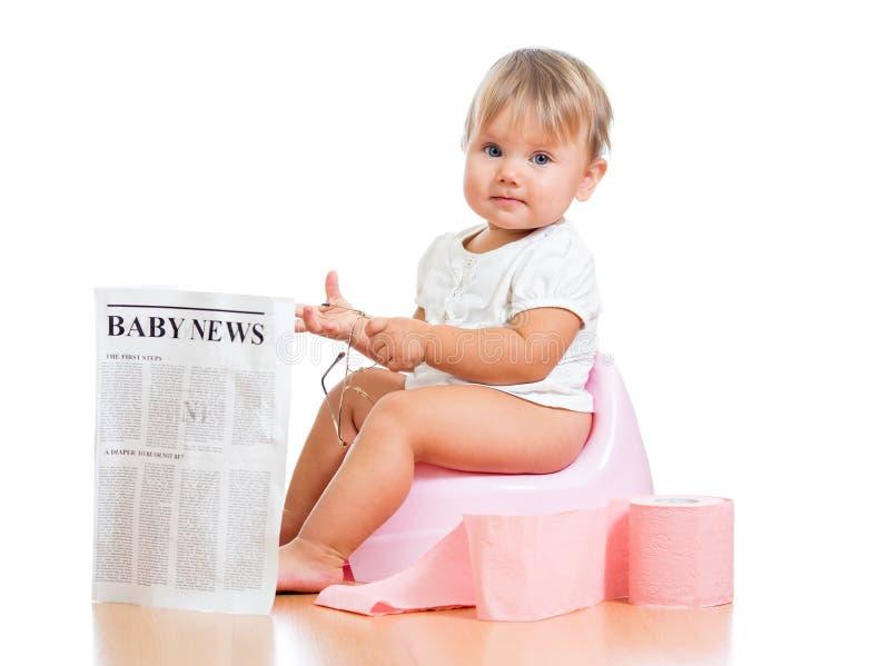 在chamberpot的滑稽的女婴读取报纸 免版税库存图片
