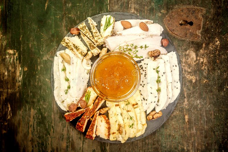 在chees的各种各样的类型的石分类的乳酪盘子与坚果、蜂蜜和莓果的 家庭做的乳酪农夫 r 免版税图库摄影