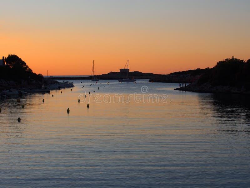 在ciutadella的卡拉市santandria在与发光的微明橙色平衡在海湾的黑暗的镇静水反映的天空与小船的和 免版税库存图片