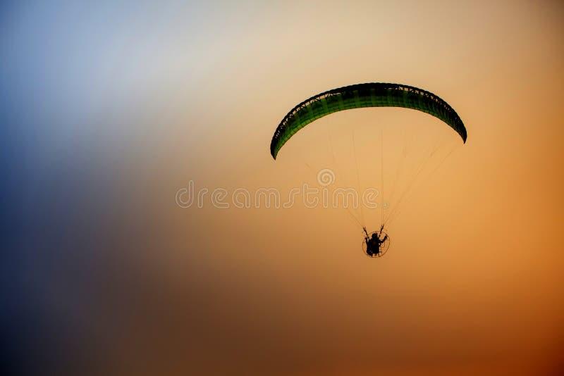 在coloful天空的人飞行由paramotor风筝,极端活动口岸 库存图片
