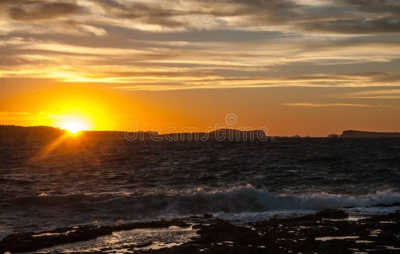 在Conejera海岛后的金黄日落 拜雷阿尔斯海搅动浪潮起伏的水在沿岸的岩石挥动 图库摄影