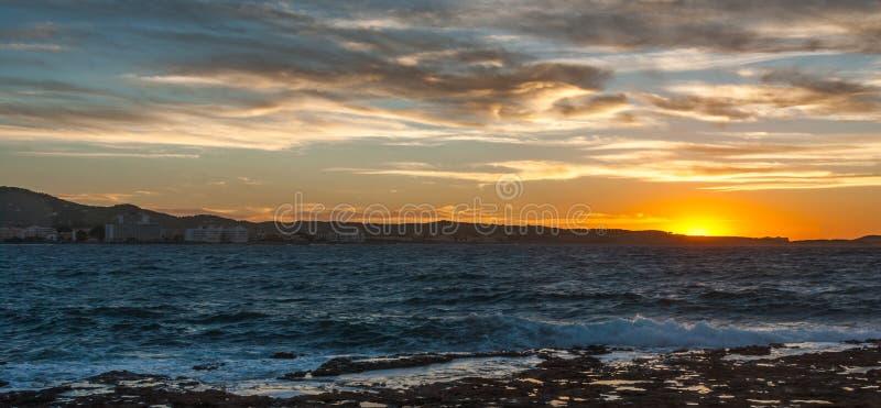 在Conejera海岛后的金黄日落 拜雷阿尔斯海搅动浪潮起伏的水在沿岸的岩石挥动 Conejera海岛看法  免版税图库摄影