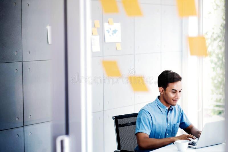 在Conputer膝上型计算机的年轻亚洲商人工作在办公室候选会议地点 免版税库存照片