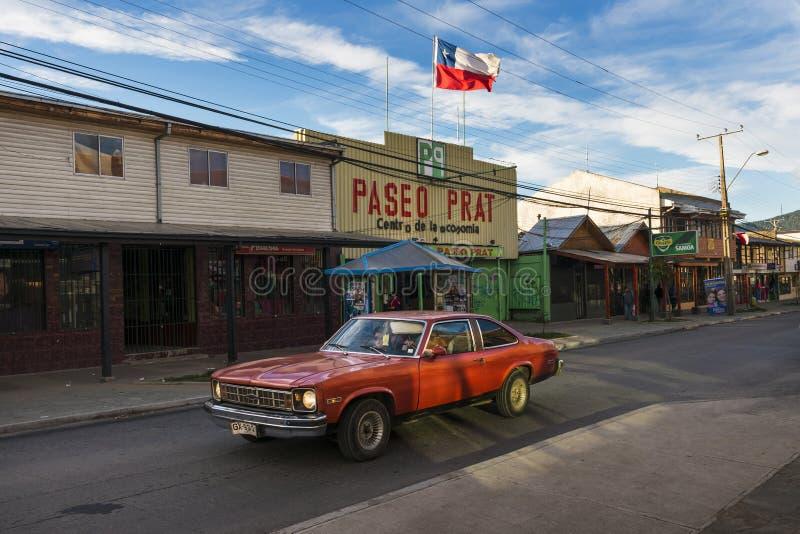 在Coyhaique镇的街道的一辆红色汽车在智利,南美 免版税库存图片