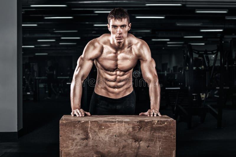 在crossfit健身房的英俊的肌肉人锻炼 免版税库存照片