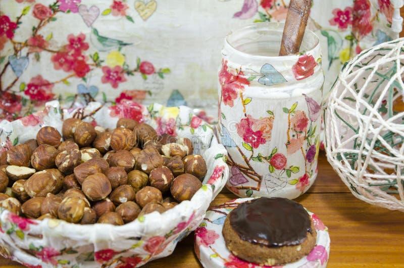 在decoupage的榛子装饰了在被围拢的桌上的碗  免版税库存图片