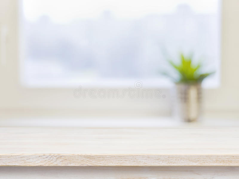 在defocuced冬天窗口背景的木桌 免版税库存图片