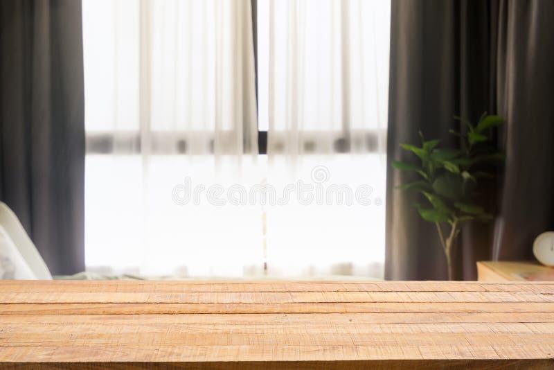 在Defocused卧室和帷幕窗口的木桌与阳光在清早 对蒙太奇产品显示或设计钥匙 库存照片