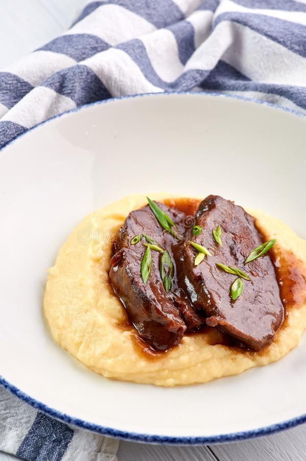 在Demiglas调味汁的猪肉面颊用土豆泥 Carrillada在demi糖渍的调味汁的de cerdo 免版税库存照片
