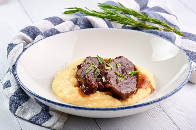在Demiglas调味汁的猪肉面颊用土豆泥 Carrillada在demi糖渍的调味汁的de cerdo 库存照片