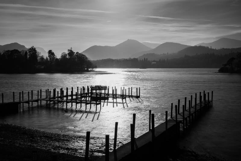 在Derwentwater湖的剧烈的黑白日落在有阴霾的湖区在山 图库摄影