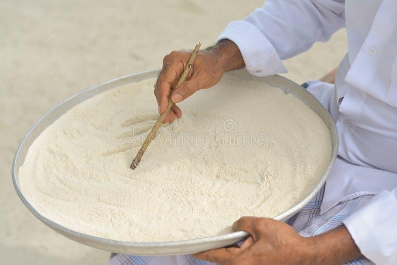 在dhivehi的马尔代夫老师文字在使用木棍子的沙子 库存照片