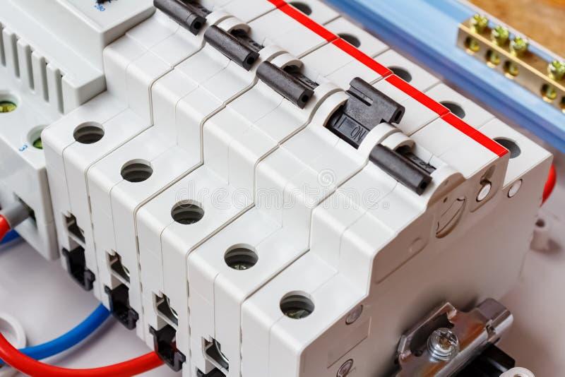 在DIN路轨的安装的自动开关在白色塑料登上的箱子特写镜头 库存照片