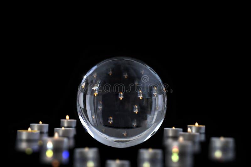 在divinationInterpretation梦想,通灵,算命不可思议的水晶球点燃的反射和蜡烛  图库摄影
