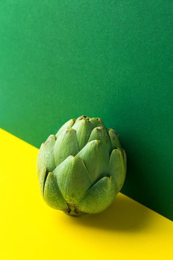 在duotone黄绿色配色背景的成熟朝鲜蓟芯 创造性的食物海报 r o 库存照片