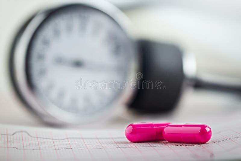 在ECG、心电图和心脏病测量仪背景的医疗药片  Diagonics、预防和治疗心血管 库存照片